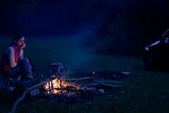 Mulher que pensa perto do fogo do acampamento Imagem de Stock Royalty Free