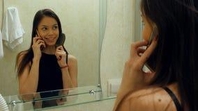 A mulher que penteia seu cabelo, enfeita-se e falando com seu amigo através do smartphone em um banheiro do hotel Fotografia de Stock