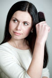 Mulher que penteia seu cabelo longo com hairbrush Imagens de Stock Royalty Free