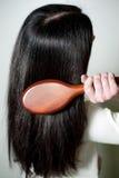 Mulher que penteia seu cabelo longo com hairbrush Imagem de Stock Royalty Free