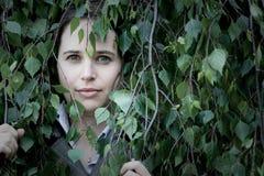 Mulher que perscruta através das folhas Foto de Stock