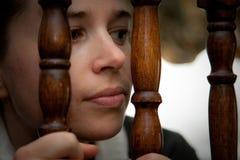 Mulher que perscruta através dos trilhos da escada Imagem de Stock