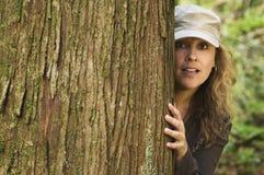 Mulher que perscruta em torno da árvore Imagens de Stock Royalty Free