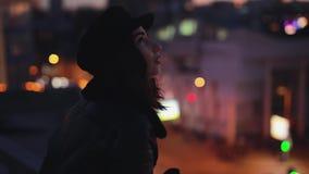 A mulher que a posição no terracce olha aprecia ao redor a calma da cidade da noite filme