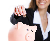 Mulher que põr a moeda em um banco piggy Fotografia de Stock Royalty Free