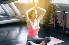 Mulher que pratica fazendo o exercício do exercício da ioga em seguida no gym, no conceito saudável e do estilo de vida fotos de stock