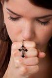 Mulher que praying com uma cruz Fotografia de Stock Royalty Free
