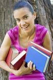 Mulher que prende muitos livros Foto de Stock
