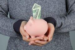 Mulher que prende o banco Piggy com dólar Foto de Stock