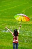A mulher que prende o guarda-chuva multicolor relaxa no campo Imagens de Stock