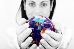 Mulher que prende o mundo em suas mãos Foto de Stock Royalty Free