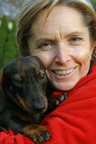 Mulher que prende um cão imagens de stock royalty free