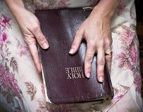 Mulher que prende uma Bíblia em seu regaço fotos de stock royalty free
