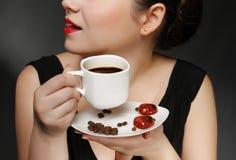 Mulher que prende uma chávena de café Foto de Stock