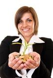 Mulher que prende uma planta crescente e moedas fotografia de stock royalty free