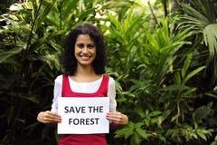 Mulher que prende uma salvaguarda o sinal da floresta Fotografia de Stock Royalty Free