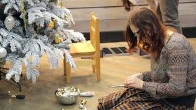 Mulher que prepara as decorações do Natal que sentam-se no assoalho dentro do estúdio filme