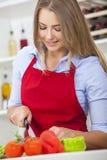 Mulher que prepara o alimento da salada dos vegetais na cozinha Imagem de Stock Royalty Free