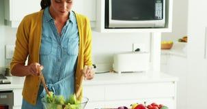 Mulher que prepara o alimento junto na cozinha video estoque