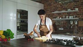 Mulher que prepara o café da manhã, cortando o baguette em uma placa na cozinha video estoque
