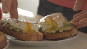 Mulher que prepara o café da manhã saudável com o abacate no pão, em ovos e no tomate roasted vídeos de arquivo