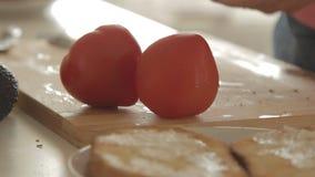 Mulher que prepara o café da manhã saudável com o abacate no pão, em ovos e no tomate roasted filme
