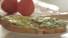 Mulher que prepara o café da manhã saudável com o abacate no pão, em ovos e no tomate roasted video estoque