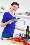 Mulher que prepara o prato da massa e que verifica a receita em uma tabuleta Fotos de Stock Royalty Free