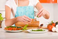 Mulher que prepara sanduíches saudáveis frescos em h Imagens de Stock Royalty Free