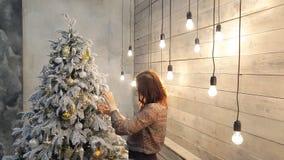 Mulher que prepara-se aos feriados para decorar dentro brinquedos do Natal vídeos de arquivo