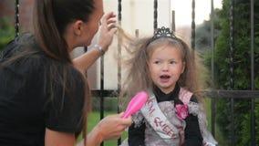 Mulher que prepara sua filha a Dia das Bruxas Menina nova do cutie que tem o divertimento Halloween feliz filme
