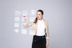 Mulher que pressiona multimédios e ícones do entretenimento em um fundo virtual Foto de Stock Royalty Free