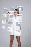 Mulher que pressiona multimédios e ícones do entretenimento em um fundo virtual Foto de Stock