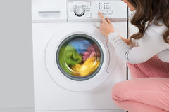 Mulher que pressiona o botão da máquina de lavar foto de stock royalty free