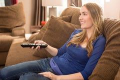 Mulher que presta atenção à tevê Fotografia de Stock Royalty Free