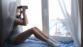 Mulher que presta atenção através dos binóculos vídeos de arquivo