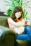Mulher que presta atenção à tevê em casa Imagem de Stock