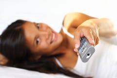 Mulher que presta atenção à tevê na cama Imagens de Stock
