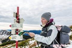Mulher que procura a maneira direita no mapa nas montanhas Imagem de Stock