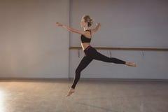 Mulher que pula ao executar esticando o exercício fotografia de stock