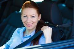 Mulher que puxa no seatbelt dentro do carro preto Conduzindo a segurança fotos de stock