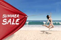 Mulher que puxa uma bandeira da venda do verão Imagem de Stock
