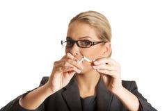 Mulher que quebra o cigarro para parar de fumar imagens de stock