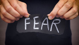 Mulher que rasga a palavra do medo escrita no papel preto imagem de stock royalty free