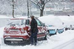 Mulher que raspa a neve congelada de suas janelas de carro Foto de Stock