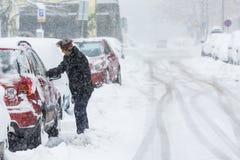 Mulher que raspa a neve congelada de suas janelas de carro Fotos de Stock Royalty Free