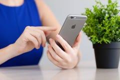Mulher que realiza no cinza do espaço do iPhone 6 da mão Imagens de Stock Royalty Free