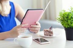 Mulher que realiza no eReader Kindle Paperwhite da mão Fotografia de Stock
