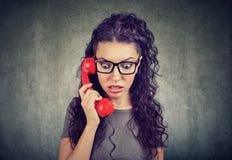 Mulher que recebe notícia chocante em um telefone que sente ansioso imagens de stock royalty free