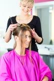 Mulher que recebe o corte de cabelo do cabeleireiro ou do cabeleireiro Foto de Stock